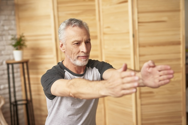 Exercises gray haired man stretching muscles.