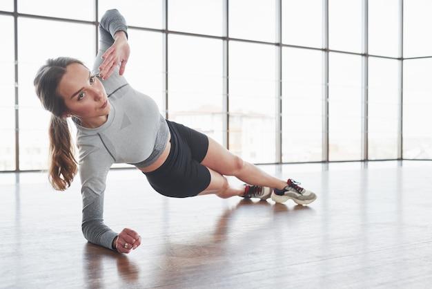 Esercizi per forza e resistenza. la giovane donna allegra ha una giornata di fitness in palestra al mattino