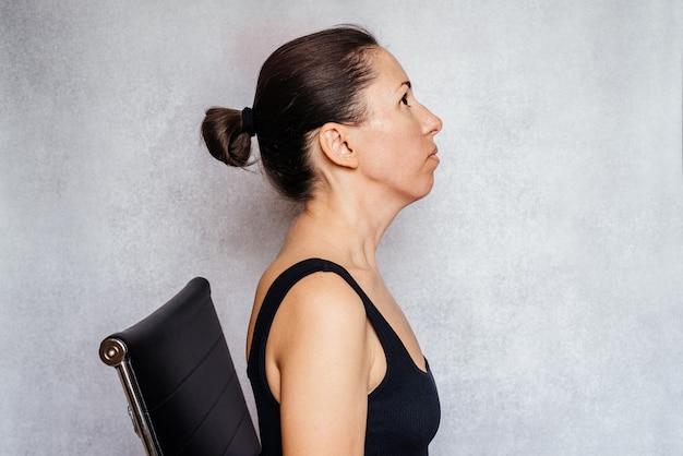 목 통증을 완화하는 운동, 목에 맥켄지법 운동을 하는 동안 여성이 부드럽게 목을 당기고, 목 통증 완화 운동을 합니다.