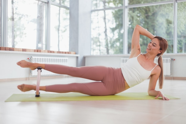 Exercises with pilates ring. woman doing aerobics workout at sport gym with panoramic windows