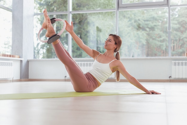 Exercises with pilates ring. woman doing aerobics workout at sport gym with panoramic windows.