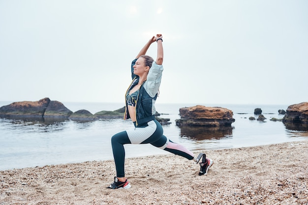 Упражнения с видом сбоку восхода солнца красивой женщины-инвалида в спортивной одежде с протезом