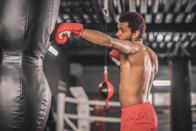 Exercising. african american kickboxer exercising in a gym working on his kicks