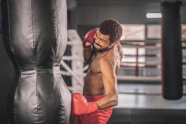 Занятия спортом. афро-американский кикбоксер тренируется в тренажерном зале, работая над его ногами