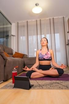 온라인 수업에서 집에서 운동, 요가를하는 금발의 백인 여자는 매트에 그녀의 거실에서 호흡