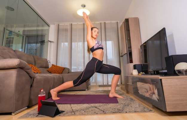 온라인 수업에서 집에서 운동, 백인 금발 무릎 꿇는 매트에 그녀의 거실에서 운동을