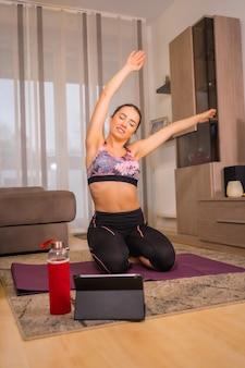 무릎을 꿇고 매트에 그녀의 거실에서 운동을하는 온라인 수업, 금발 백인 여자와 함께 집에서 운동