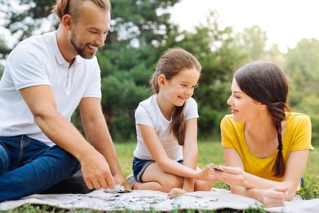 두뇌 운동. 초원의 잔디에 앉아 함께 퍼즐을 풀고 필요한 조각으로 서로를 돕는 행복한 사랑스러운 가족