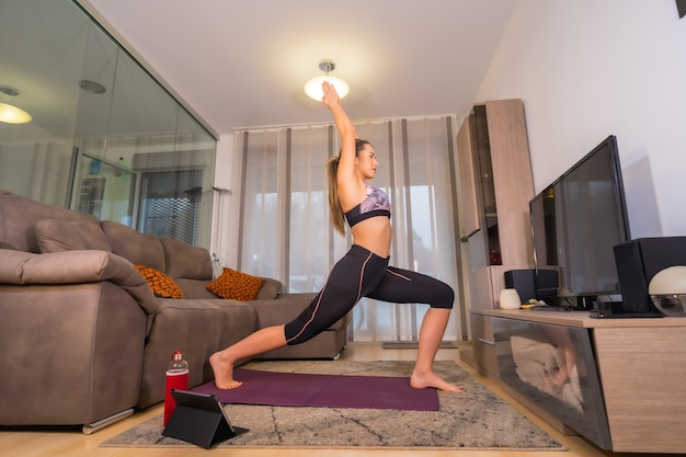 Exercising at home in an online class, caucasian blonde doing exercises in her living room on the kneeling mat
