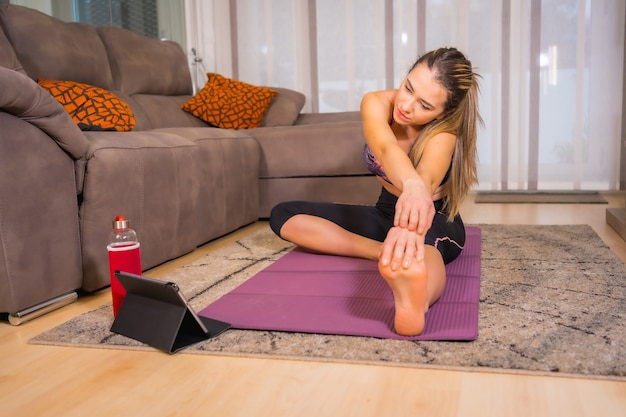 Exercising at home with in an online class, caucasian woman doing yoga exercises at home on the mat