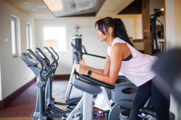 Exercising legs doing cardio workout on cycling bike