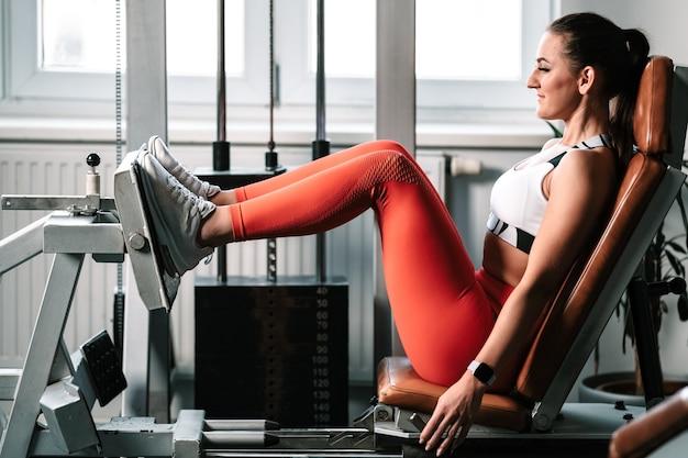 ジムのマシンで脚を鍛える、女性フィットネスインストラクター
