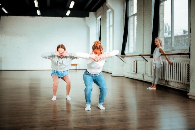 運動。ブルージーンズをはいたプロのバレエ教師と腕の動きをする生徒