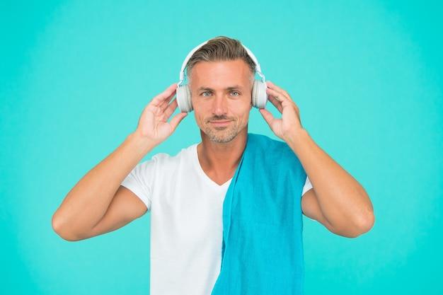 음악에 운동. 잘생긴 남자는 파란색 배경에서 음악을 즐깁니다. 운동 남자는 헤드폰으로 음악을 듣습니다. 음악을 들으면 운동이 향상됩니다. 체육관에서 훈련.