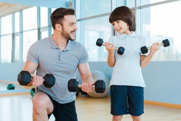 一緒に運動する。幸せな父と息子がダンベルで運動し、ヘルスクラブに立っている間笑顔