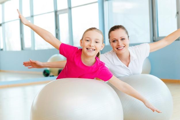 一緒に運動するのは楽しいです。陽気な母と娘がフィットネスボールで運動し、カメラを見て