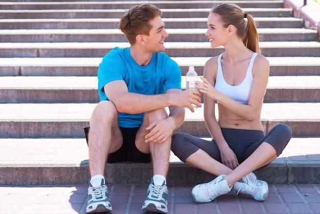 Тренироваться вместе - это весело. вид сбоку красивой молодой пары в спортивной одежде, сидящей на лестнице лицом к лицу и улыбающейся