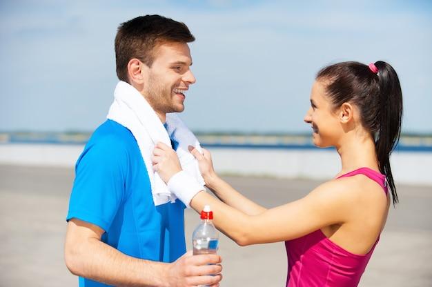 Тренироваться вместе - это весело. вид сбоку красивой молодой пары в спортивной одежде, стоящей лицом к лицу и улыбающейся