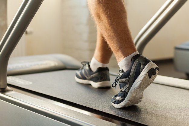 Exercising on treadmill. close-up of man walking by treadmill in sports club