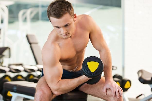 ダンベルで運動する。ジムでダンベルを使ってトレーニングする自信のある若い筋肉の男