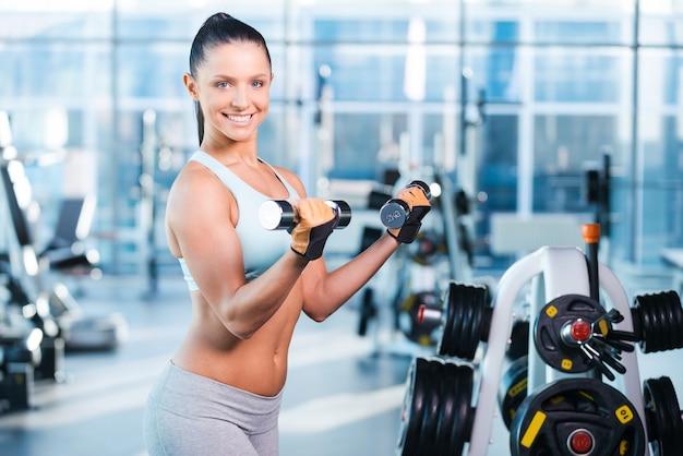 Упражнения с гантелями. счастливая молодая женщина тренируется с гантелями и улыбается, стоя в тренажерном зале
