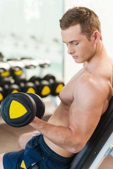 ダンベルで運動する。ジムでダンベルを使ってトレーニングしている自信を持って若い筋肉の男の背面図
