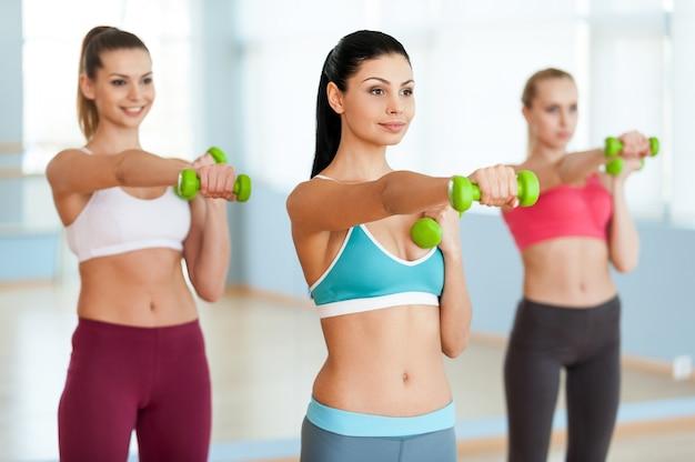 ダンベルで運動する。スポーツウェアの3人の美しい若い女性
