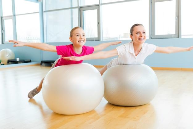 フィットネスボールで運動する。陽気な母と娘がフィットネスボールで運動し、笑顔