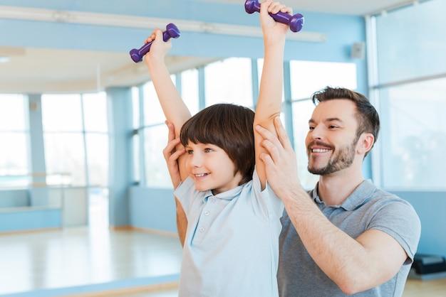 楽しく運動する。両方がヘルスクラブに立っている間、ウエイトトレーニングで息子をサポートする幸せな父