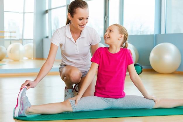 강사와 함께 운동. 스포츠 클럽에서 스트레칭 운동으로 어린 소녀를 돕는 쾌활한 강사