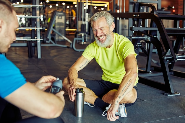 Exercising with personal trainer happy middle aged man discussing something with fitness instructor