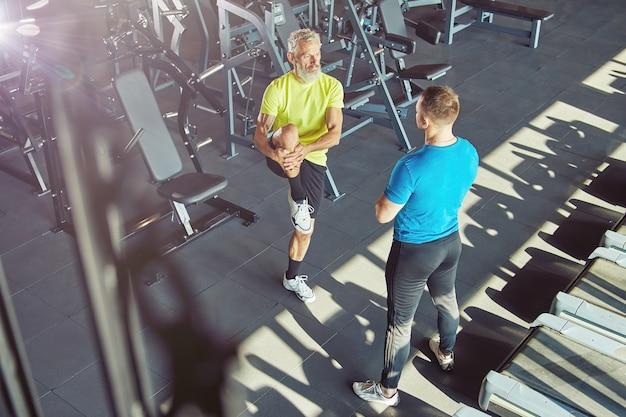 スポーツウェアの中年男性のパーソナルトレーナーと一緒に運動し、足を伸ばしてウォーミングアップし、