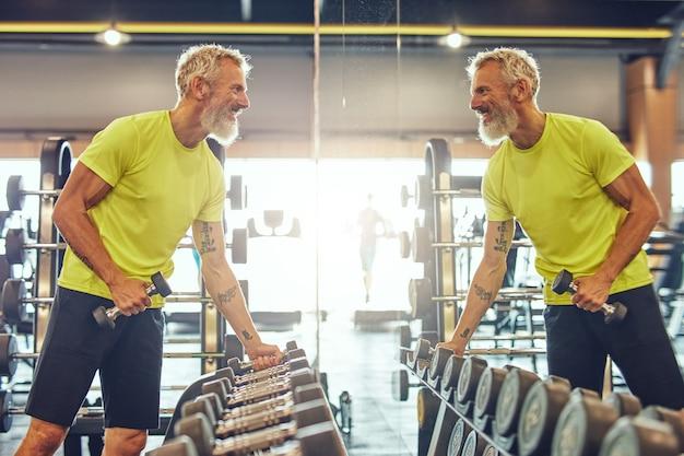 아령 찾고 운동복에 잘 생긴 성숙한 남자의 무게 측면보기와 운동