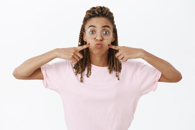 Espira lo stress. ritratto di giovane donna afroamericana giocosa e carina spensierata in bicchieri con i dreadlocks imbronciato trattenendo il respiro