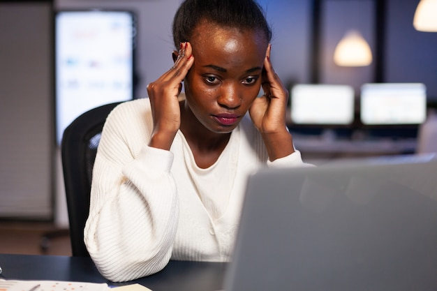 Exhausted african entrepreneur analysing financial revenues laptop working overtime