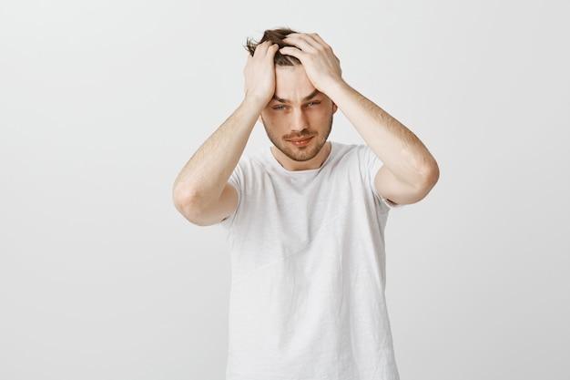 Измученный и огорченный молодой человек хватается за голову и выглядит усталым
