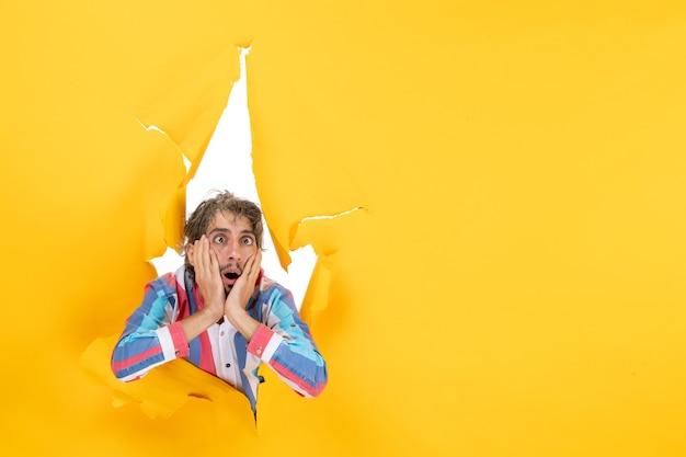 引き裂かれた黄色の紙の穴の背景に疲れた感情的な若い男のポーズ