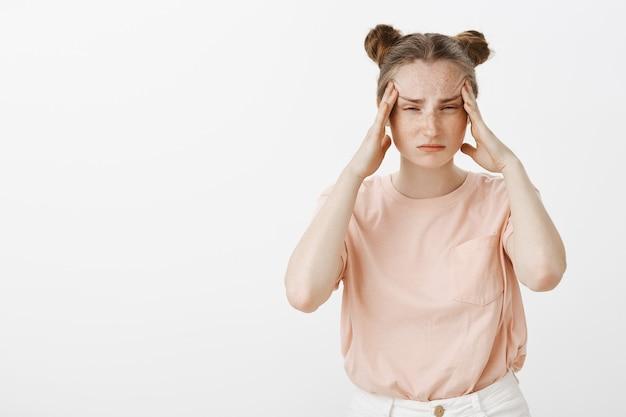 Изможденная и перегруженная работой девочка-подросток позирует у белой стены