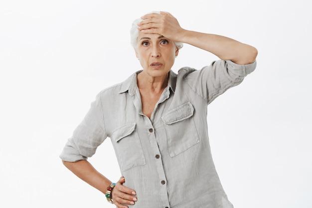 Измученная и шокированная бабушка шлепает по лбу и выглядит обеспокоенной