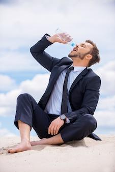 Измученный и жаждущий. молодой бизнесмен пьет воду, сидя на вершине песчаной дюны