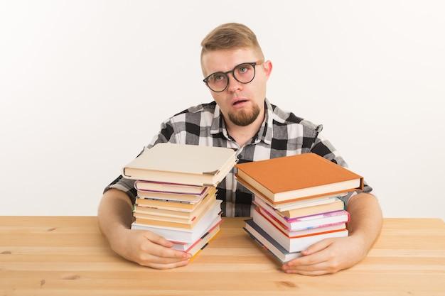 Измученный и усталый студент, одетый в клетчатую рубашку, сидит