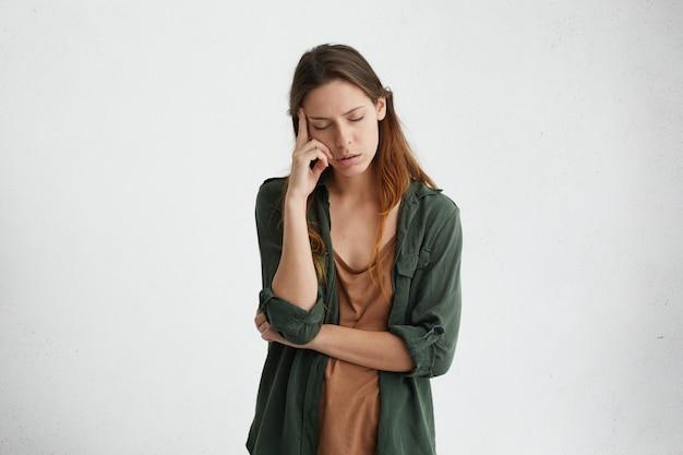Измученная и уставшая женщина с темными волосами, стоящая у белой стены с закрытыми глазами, держа указательный палец на виске, думает о чем-то. расстроенная женщина с усталым выражением лица.