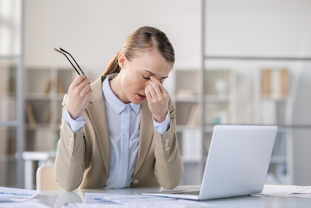 Exhausted attractive young woman in jacket tired from work with computer sitting at table and rubbing bridge of nose while taking off eyeglasses, eye fatigue concept