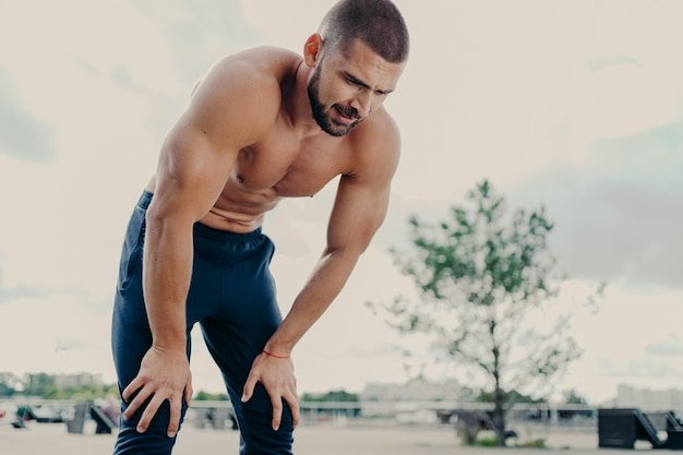 Exhausted bearded man jogger has rest after long distance running, breathes deeply, takes break during running, has muscular strong body, poses outside.