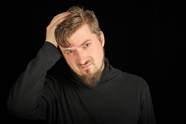 Exhausted bearded man portrait with headache, black background. overworking, head pain concept. young guy in black polo neck sweater. exhausted and tired to point of anger man.