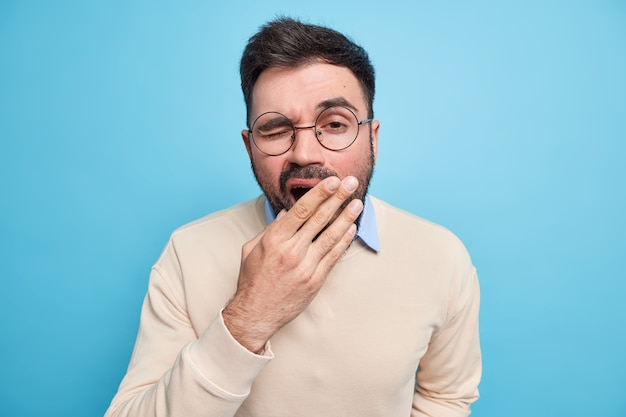 Exhausted bearded young man covers mouth and yawns after having sleepless night has tired expression after working late hours dressed in sweater round eyeglasses