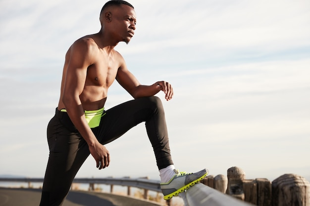 지친 흑인 남성 러너는 활발한 달리기 후 휴식을 취하고 운동화를 신고 포즈를 취하고 미래의 스포츠 경기에 대해 생각하며 힘든 스포츠 운동을합니다. 조깅과 동기 부여