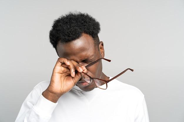 疲れ果てた黒人男性がラップトップの過労で仕事をした後、目をこすりながら眼鏡を外すと疲れを感じる