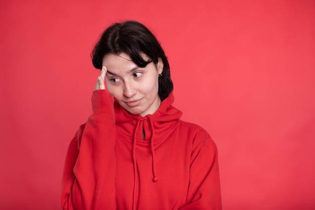 Exhausted brunette girl in red hoodie touches forehead looking at front