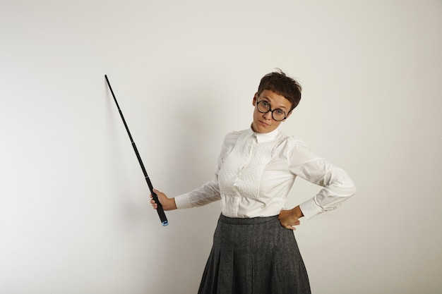 Exhausted and burnt out female teacher in old-fashioned clothing standing by a whiteboard with a pointer